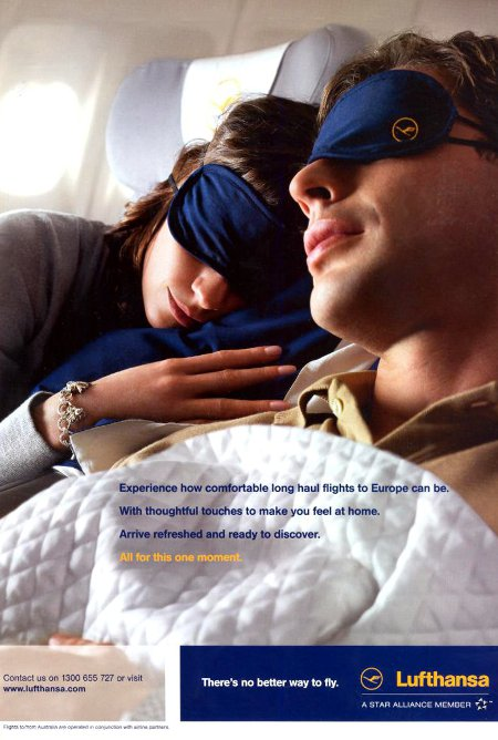 Lufthansa advertisement titled '...all for this one moment', featuring a couple of passengers comfortably sleeping in Business Class seats.